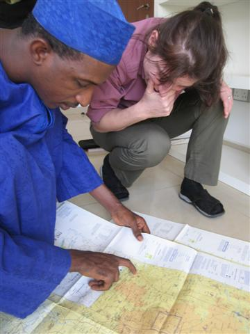 Saleh and Esther look at a map of Abuja's surroundings
